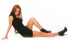 The blonde in a black dress lays on a white Stock Photos