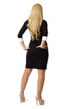 Blonde in black dress is standing with his back. Royalty Free Stock Photography