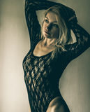 Blonde in black lace. Blond woman in black lace looking towards the light royalty free stock photo