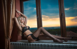Blonde in black lingerie posing provocatively in window frame Stock Photos