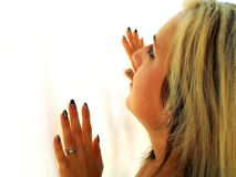 Blonde, black ombre haired and blue eyed young woman from the side with white texture background. His hands in front of him royalty free stock photos