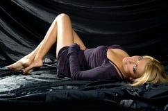 Blonde on black satin fabrics Stock Photo