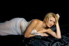 Blonde on black satin fabrics Royalty Free Stock Photos