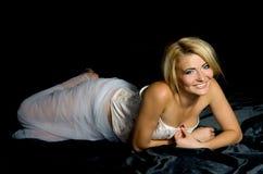 Blonde on black satin fabrics Stock Photos