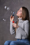 Blonde blowing bubbles. Close up. Gray background Stock Photo