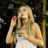 Blonde blowing soap bubble Royalty Free Stock Image