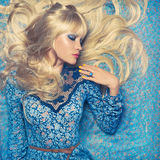 Blonde on Blue. Beautiful sensual blonde lying on a blue pattern Stock Image