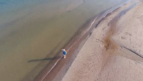 Blonde in a blue dress walks on the water on the beach of the Baltic Sea, early in the morning. Sunny day. Long shadows. Aerial shooting from the drone stock footage