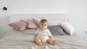 Blonde blue eyed infant is sitting in a large bed with baby pacifier and looking forward in daytime in cozy home stock video footage