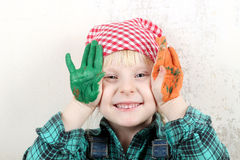 Blonde blue-eyed little girl  with hands in the paint Royalty Free Stock Photo