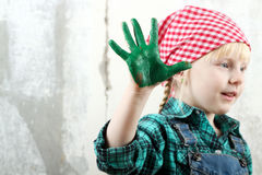 Blonde blue-eyed little girl  with hands in the paint Royalty Free Stock Photos