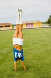 Blonde in Blue Football Jersey. Blonde female fashion model in blue football jersey doing a handstand Royalty Free Stock Photo