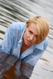 Blonde in blue shirt near riv Royalty Free Stock Photos