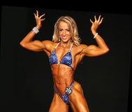 Blonde Bodybuilder Flashes Big Smile and Peaked Biceps Royalty Free Stock Images