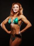 Blonde Bodybuilderfrau im bikin auf schwarzem Hintergrund Stockfotos