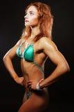 Blonde Bodybuilderfrau im bikin auf schwarzem Hintergrund Stockbilder