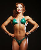 Blonde Bodybuilderfrau im bikin auf schwarzem Hintergrund Lizenzfreie Stockfotografie