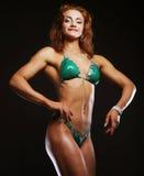 Blonde Bodybuilderfrau im bikin auf schwarzem Hintergrund Stockfotografie