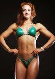 Blonde Bodybuilderfrau im bikin auf schwarzem Hintergrund Lizenzfreie Stockfotos