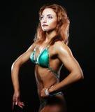 Blonde Bodybuilderfrau im bikin auf schwarzem Hintergrund Lizenzfreies Stockfoto
