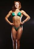 Blonde Bodybuilderfrau im bikin auf schwarzem Hintergrund Stockbild
