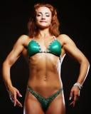 Blonde Bodybuilderfrau im bikin auf schwarzem Hintergrund Stockfoto