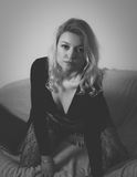Blonde in bolero. Blond woman in bolero and lace stockings on sofa royalty free stock photography