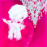Blonde bombshell on red and pink abstract background. This classic blonde bombshell  poses in front of a crystal chandelier, dazzling Hollywood with her red Royalty Free Stock Photo