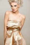 Blonde bonito no vestido do ouro Imagem de Stock Royalty Free