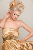 Blonde bonito no vestido do ouro Imagens de Stock