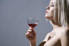 Blonde bonito que prende um vidro do vinho vermelho Imagem de Stock