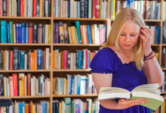 Blonde bookreader in studie stock foto