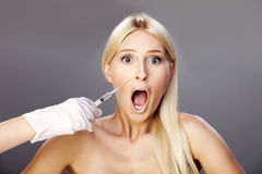 Blonde and botox 2. Young blonde getting botox injection, with the scared expression on her face Stock Photos