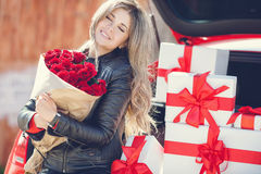 Blonde with a bouquet of flowers and gifts Stock Image