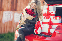 Blonde with a bouquet of flowers and gifts Stock Photography