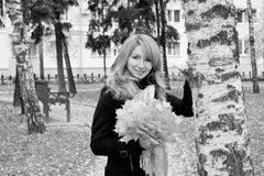 Blonde with  bouquet from leaves in  park. Blonde with a bouquet from leaves in a park Stock Image