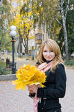 Blonde with  bouquet from yellow leaves. Blonde with a bouquet from yellow leaves Stock Photo