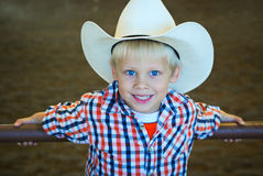 Blonde hair cowboy. Blonde boy with blue eyes and cowboy hat royalty free stock images