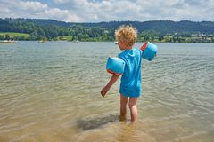 Blonde Boy With Floats Dipping His Feet In An Altitude Lake stock image