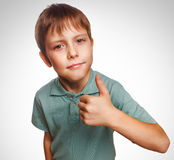 Blonde boy kid in blue shirt holding thumbs up, Royalty Free Stock Photos
