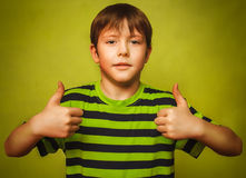 Blonde boy kid in shirt holding thumbs up, showing Stock Photos
