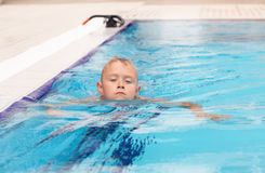 A blonde boy learning to swim stock image
