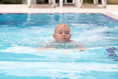 A blonde boy learning to swim stock photography