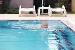 A blonde boy learning to swim stock photo