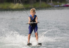 Blonde Boy learning to waterski on a lake Stock Image
