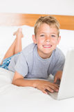 Blonde boy lying on bed using laptop smiling at camera Stock Image