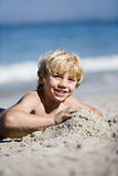 Blonde boy (7-9) lying on sandy beach, smiling, portrait Royalty Free Stock Photos