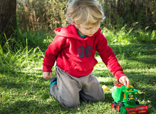 Blonde boy playing with farm toy stock photo