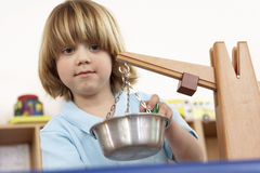 Blonde boy (4-6) playing with weight scale in classroom, close-up, low angle view Royalty Free Stock Photos