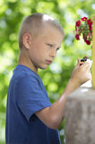 Blonde boy plays in the garden Royalty Free Stock Image